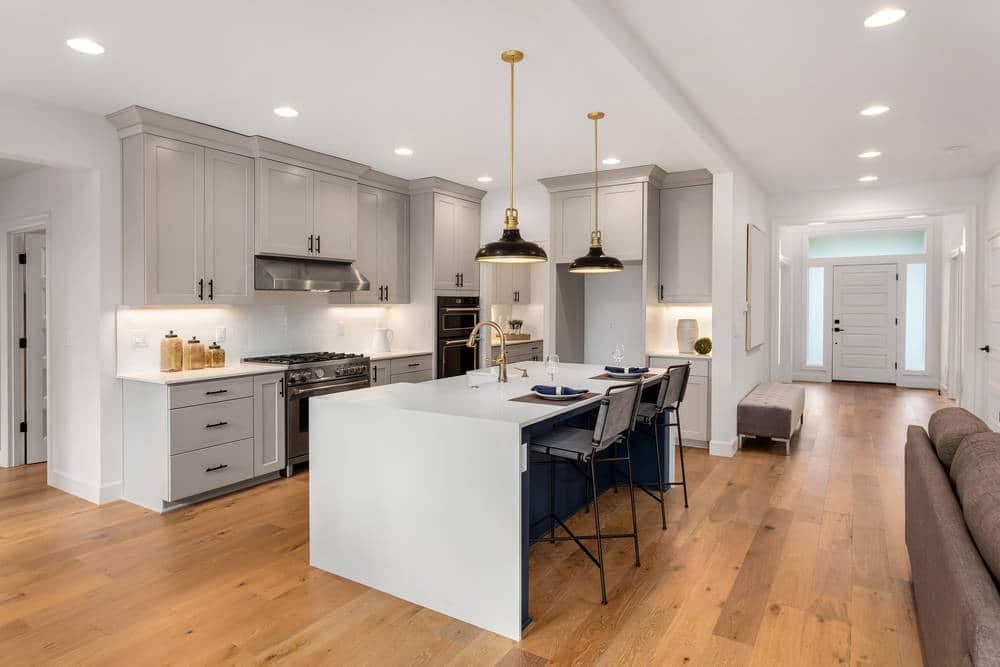 Fully restored Beautiful kitchen in flooded luxury home with waterfall island, quartz counter tops, farmhouse sink, and hardwood floors | DryCare Restoration Water Fire Mold Damage Crime Scene Cleanup, Los Angeles Ventura Orange County