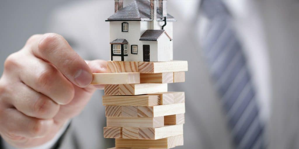 business man playing jenga with a house on top   9 types of water damage and how to restore them   DryCare Restoration Blog   Best Water Fire Mold Damage Restoration and Crime Scene Cleanup in Southern California