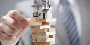 business man playing jenga with a house on top | 9 types of water damage and how to restore them | DryCare Restoration Blog | Best Water Fire Mold Damage Restoration and Crime Scene Cleanup in Southern California
