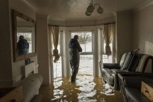 man standing in flooded home | 9 types of water damage and how to restore them | DryCare Restoration Blog | Best Water Fire Mold Damage Restoration and Crime Scene Cleanup in Southern California
